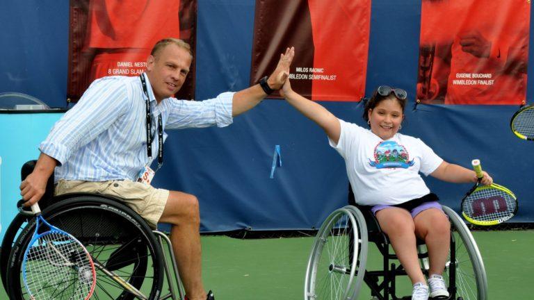 kei schrameyer hi-fives a wheelchair tennis player